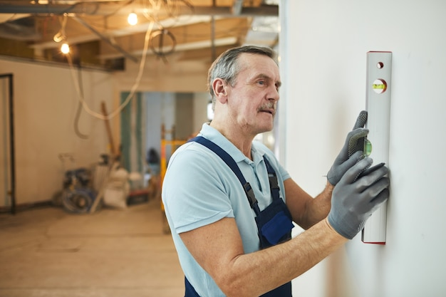 Retrato da vista lateral do trabalhador da construção civil sênior nivelando a parede durante a reforma da casa, copie o espaço
