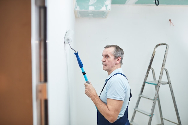 Retrato da vista lateral do trabalhador da construção civil sênior pintando a parede enquanto reforma a casa, copie o espaço