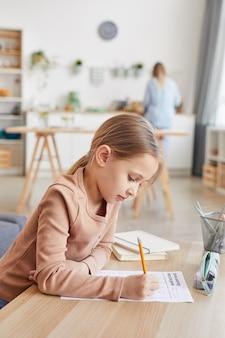 Retrato da vista lateral vertical da linda garota fazendo lição de casa para a escola primária enquanto estudava em casa em um interior aconchegante, copie o espaço