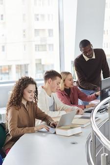 Retrato da vista lateral vertical de um grupo multiétnico de alunos usando laptops enquanto estudavam na faculdade