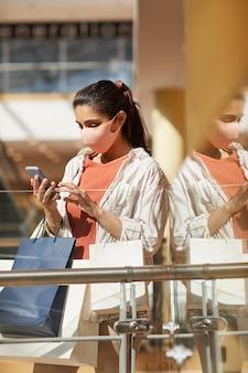 Retrato da vista lateral vertical de uma jovem usando máscara enquanto fazia compras no shopping e usando o smartphone, cena iluminada pela luz solar