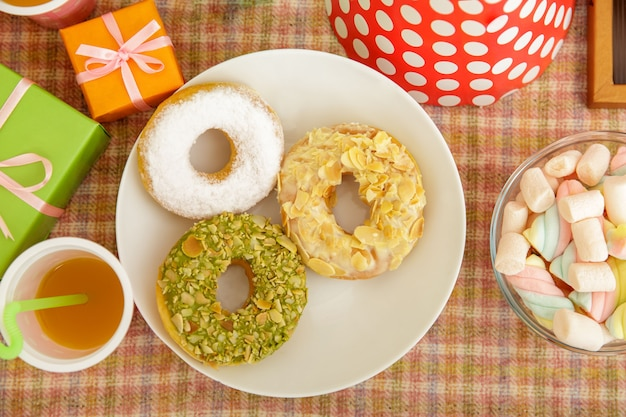 Retrato da vista superior de alguns donuts e marshmallow na mesa posta para festa infantil