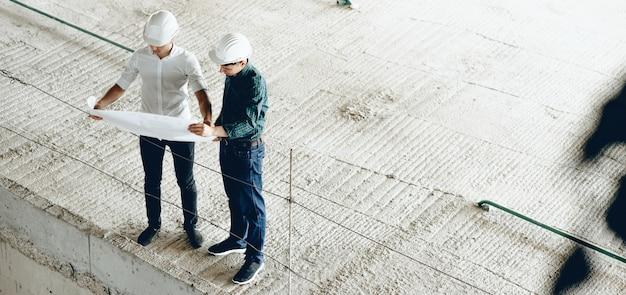 Retrato da vista superior de dois engenheiros olhando para a planta do prédio enquanto seguram um mapa