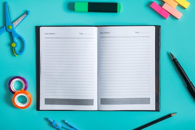 Retrato da vista superior de um caderno em branco com ferramentas de escritório em um fundo pastel