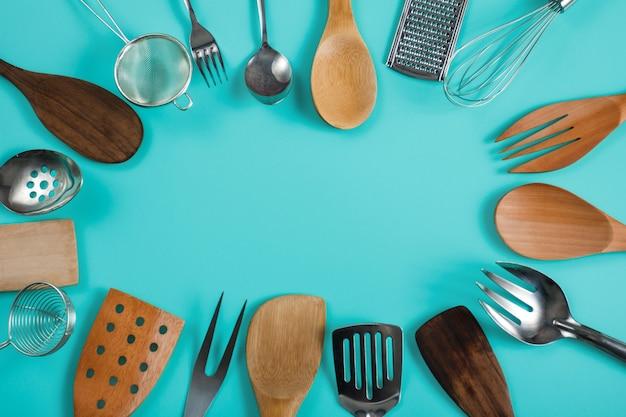 Retrato da vista superior de um grupo de utensílios de cozinha em fundo azul pastel