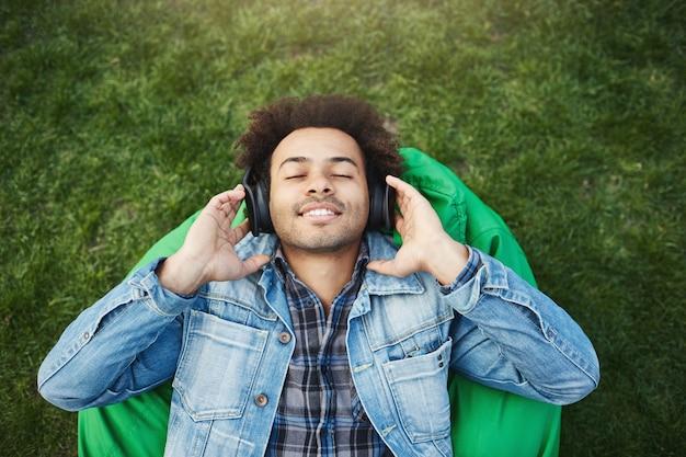 Retrato da vista superior de um homem afro-americano relaxado e satisfeito com as cerdas deitado na grama enquanto ouve música com os olhos fechados e um sorriso, sendo feliz e curtindo os sons enquanto está no parque