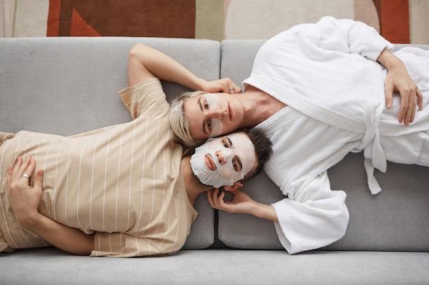 Retrato da vista superior de um jovem casal gay olhando para a câmera enquanto estão deitados no sofá juntos e usando máscaras faciais, conceito de beleza e cuidados com a pele