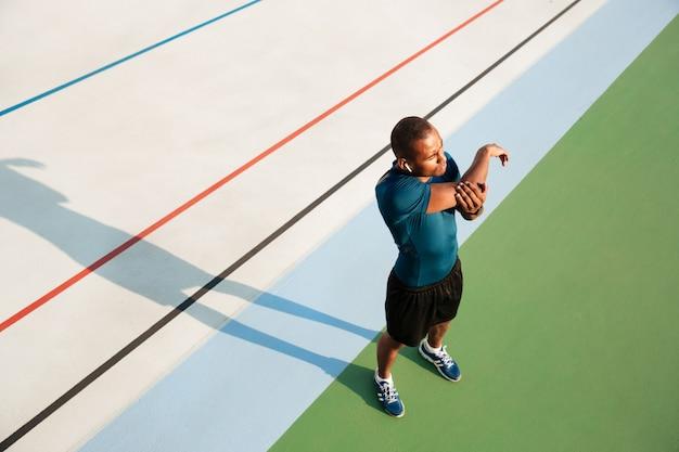 Retrato da vista superior de um jovem desportista africano alongamento
