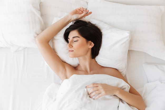 Retrato da vista superior de uma jovem sensual dormindo na cama