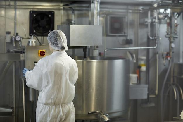 Retrato da vista traseira da jovem trabalhadora operando unidades de máquina na fábrica de produção de alimentos limpos, copie o espaço