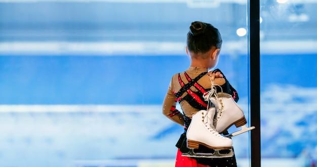 Retrato da vista traseira da menina segurando patins em pé na pista de gelo coberta