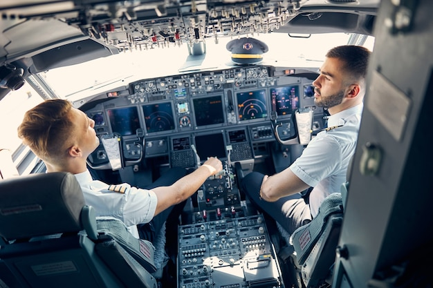 Retrato da vista traseira de dois pilotos discutindo o plano de voo para o voo deles sentados na cadeira na cabine