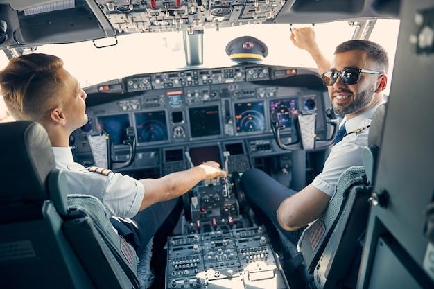 Retrato da vista traseira de dois pilotos uniformizados trabalhando enquanto um homem de óculos escuros olhando para a câmera fotográfica
