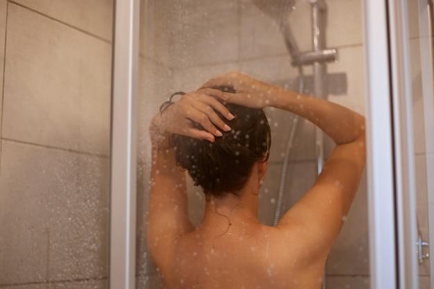 Retrato da vista traseira de mulher limosa com ombros nus tomando banho, posando de costas no banheiro, higiene pessoal, procedimentos matinais, cuidados com os cabelos e refresco.