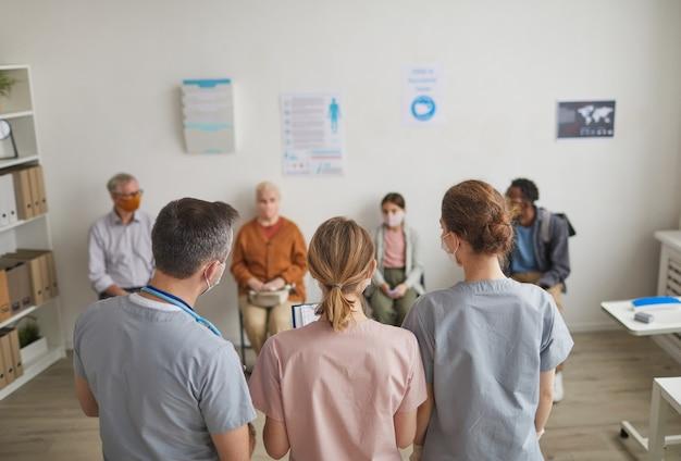 Retrato da vista traseira de um grupo de médicos olhando para pacientes que esperam na fila no centro de vacinação ou clínica, copie o espaço