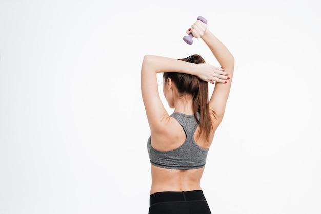 Retrato da vista traseira de uma mulher fitness malhando com halteres isolado em um fundo branco