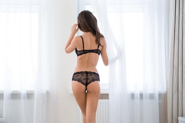 Retrato da vista traseira de uma mulher sexy em lingerie, olhando para a janela