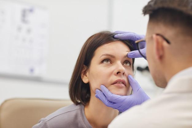 Retrato da vista traseira do jovem oftalmologista abrindo o olho de uma paciente