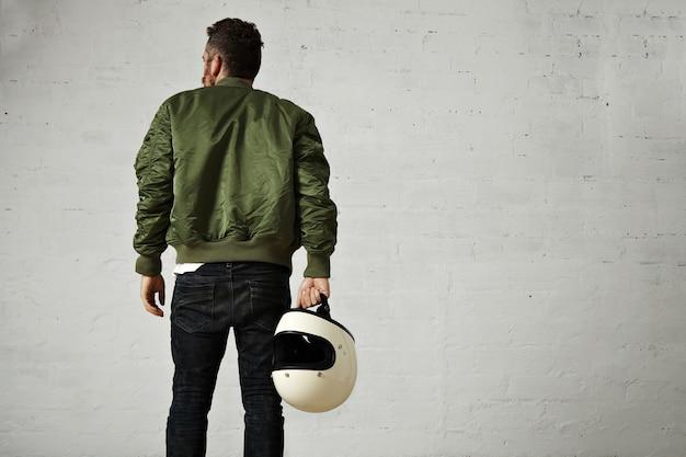 Retrato das costas de um piloto barbudo com jaqueta verde, jeans skinny e um capacete branco em branco na mão com paredes brancas