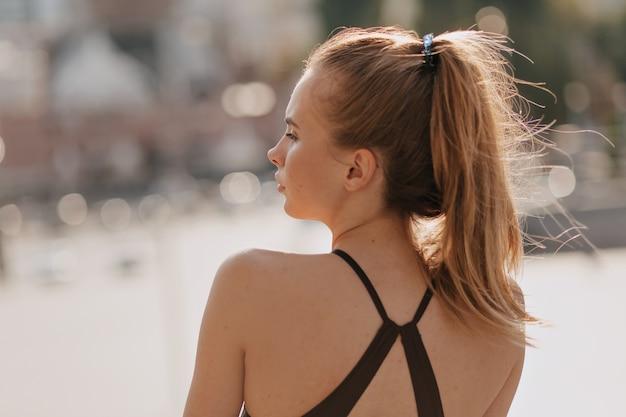 Retrato das costas de uma mulher europeia com roupas esportivas em um dia bom de sol