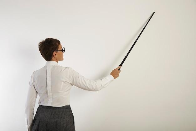 Retrato das costas de uma professora branca, de aparência séria, de blusa, saia e óculos, apontando para uma parede branca com um ponteiro preto
