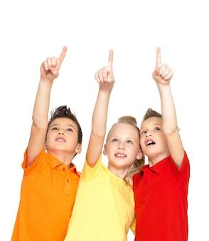 Retrato das crianças felizes apontando para cima com os dedos em algo distante - isolado no branco