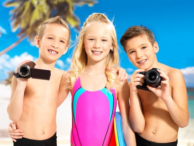 Retrato das crianças felizes desfrutando na praia. crianças em idade escolar em pé com uma câmera fotográfica e de vídeo nas mãos.