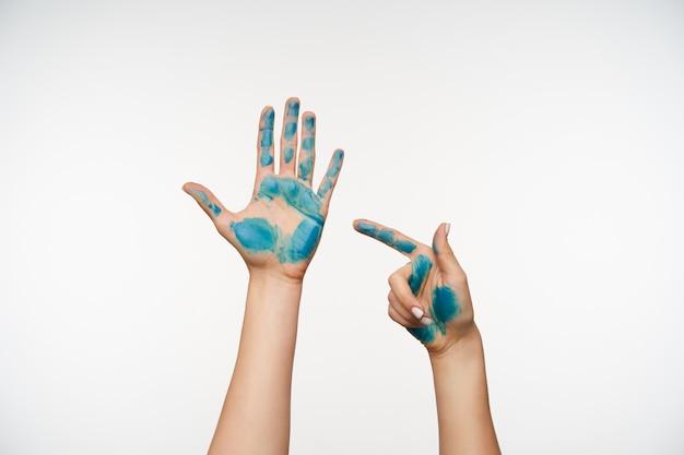 Retrato das mãos de pele clara de uma senhora bonita e levantada posando em branco, uma mão aparecendo na outra com o dedo indicador