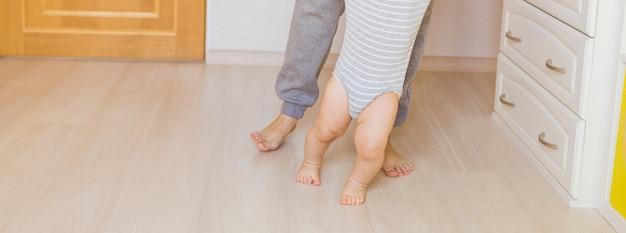Retrato das pernas da mãe e do bebê. primeiros passos.