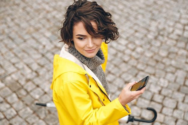 Retrato de 20 anos feminino bonito andando em pedras de pavimentação com telefone celular e guarda-chuva nas mãos, procurando a rota adequada