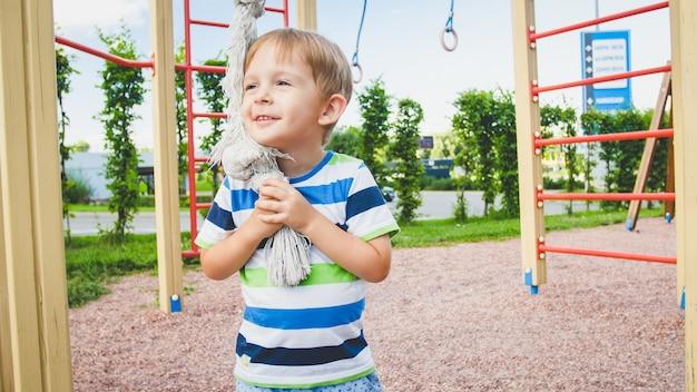 Retrato de 3 anos brincando no parquinho e tentando subir na corda grande no parque