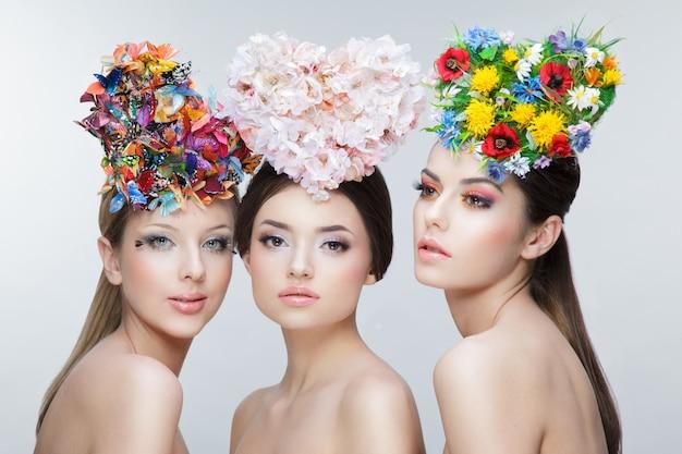 Retrato de 3 jovens posando com coroas de flores