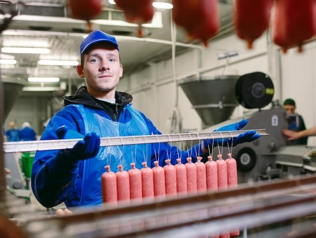 Retrato de açougueiros processando salsichas na fábrica de carne