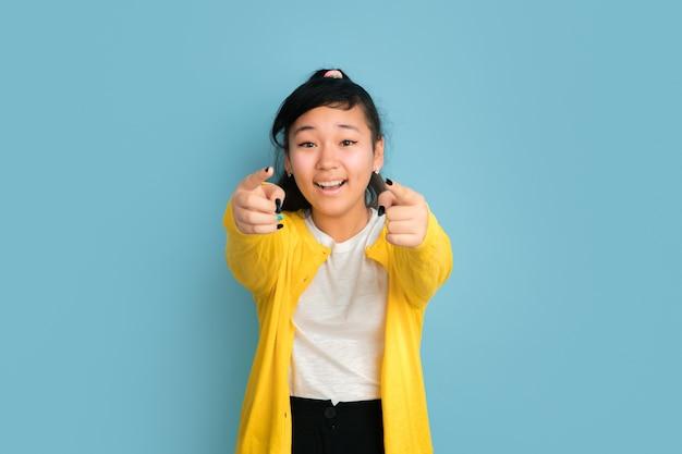 Retrato de adolescente asiático isolado no espaço azul