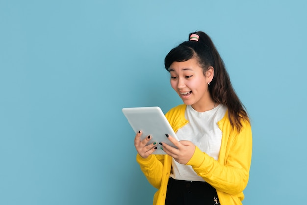 Retrato de adolescente asiático isolado no fundo azul do estúdio