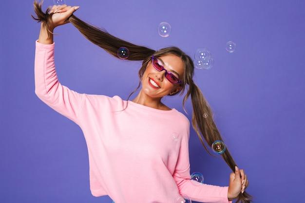 Retrato de adolescente em moletom com óculos de sol da moda, se divertindo e tocando seus rabos de cavalo