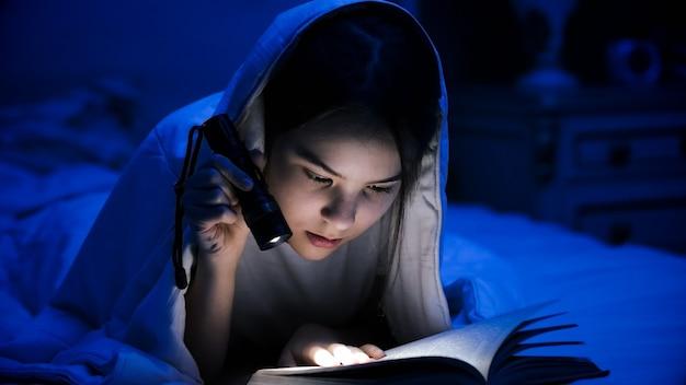 Retrato de adolescente lendo livro na cama com lanterna.