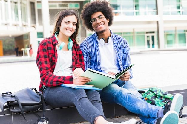 Retrato, de, adolescente, macho fêmea, estudantes, segurando, livros, em, mão, sentando, em, campus