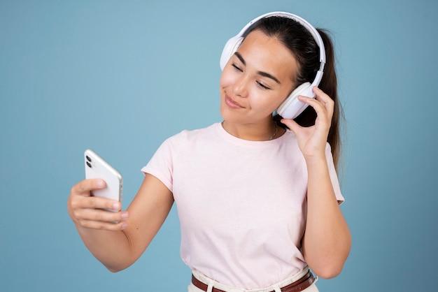 Retrato de adolescente usando fones de ouvido e smartphone