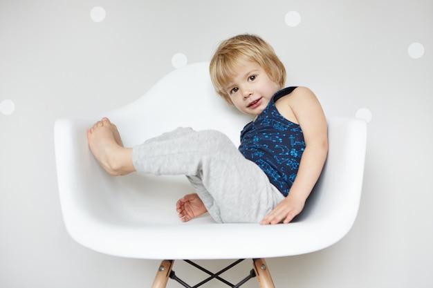 Retrato de adorável criança descalça com cabelos loiros, vestida com calça cinza e camisa sem mangas, desfrutando de passatempos infantis dentro de casa, sentado na cadeira branca, parecendo feliz e alegre.