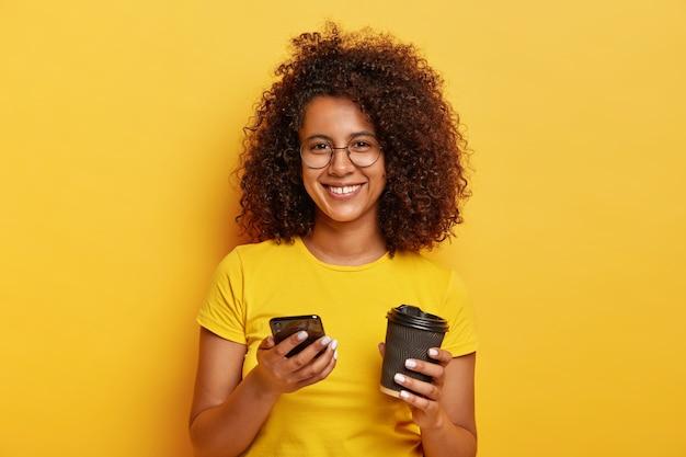 Retrato de adorável fêmea milenar segura smartphone e bebe café para viagem, sorri agradavelmente, usa camiseta amarela, pede número para um encontro mais tarde