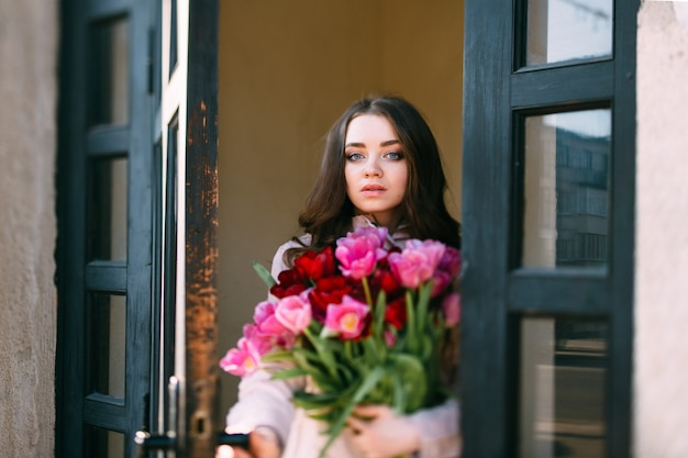 Retrato de adorável inclinação elegante na mudança da menina morena sorridente feliz com buquê de tulipas