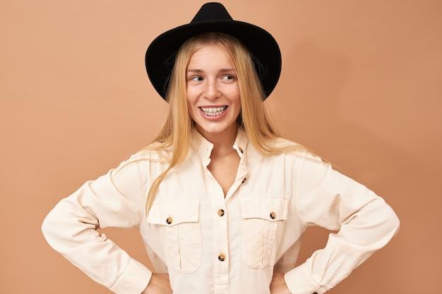 Retrato de adorável jovem caucasiana com chapéu preto posando isolada em postura determinada e confiante, mantendo as mãos na cintura, sorrindo amplamente
