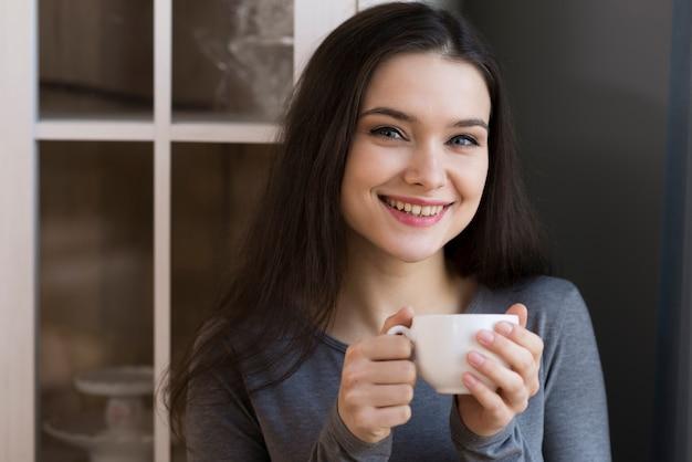 Retrato de adorável jovem segurando uma xícara de café