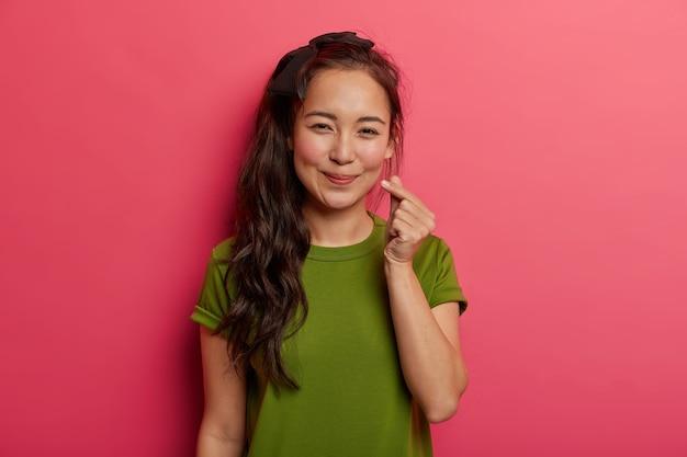Retrato de adorável menina morena espalha amor e felicidade, mostra o sinal do coração, símbolo coreano de afeto com os dedos, usa uma camiseta verde, isolado sobre um fundo rosa brilhante