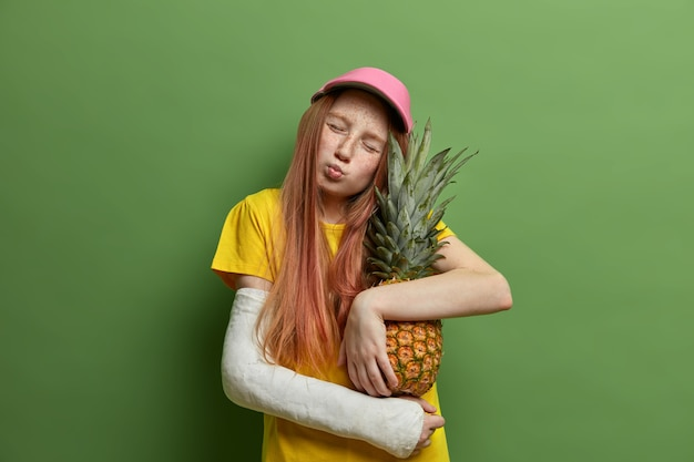 Retrato de adorável menininha sardenta inclina a cabeça, tem os olhos fechados e os lábios arredondados, abraça com amor o delicioso abacaxi, quebrou o braço depois de cair de altura, isolado na parede verde.