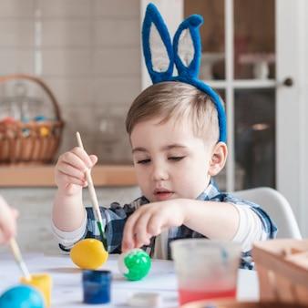 Retrato de adorável menino pintando ovos de páscoa