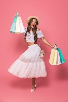 Retrato de adorável mulher morena usando chapéu de palha e saia fofa segurando pacotes de compras de papel colorido