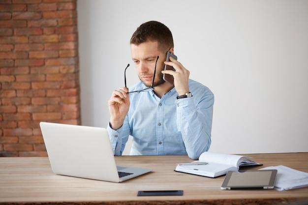 Retrato de adulto barbeado contador masculino decolando óculos, assistindo no monitor do laptop com expressão cansada