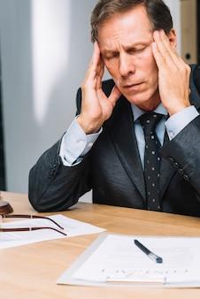 Retrato de advogado maduro estressado, tocando a cabeça no escritório